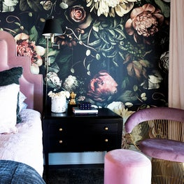 Moody pink and navy bedroom with bold, floral wallpaper and bedside pouf