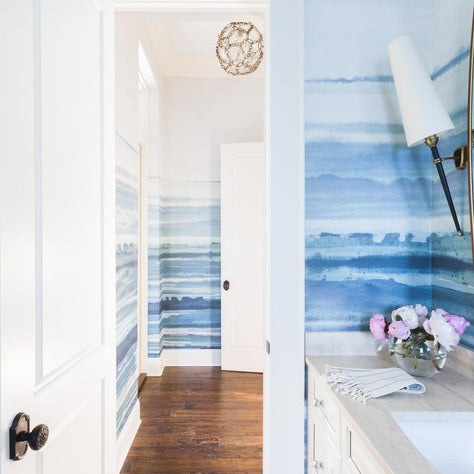 blue painterly bathroom and vestibule with gold chandelier