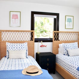 rattan headboard/twin beds/blue bedding/colorful art/tropical/vacation home