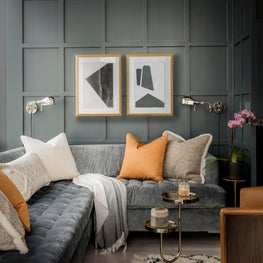 Family room with paneled wall and velvet sectional designed by Robin Gannon Interiors