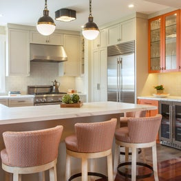 Bright orange cabinetry and designer backsplash tile
