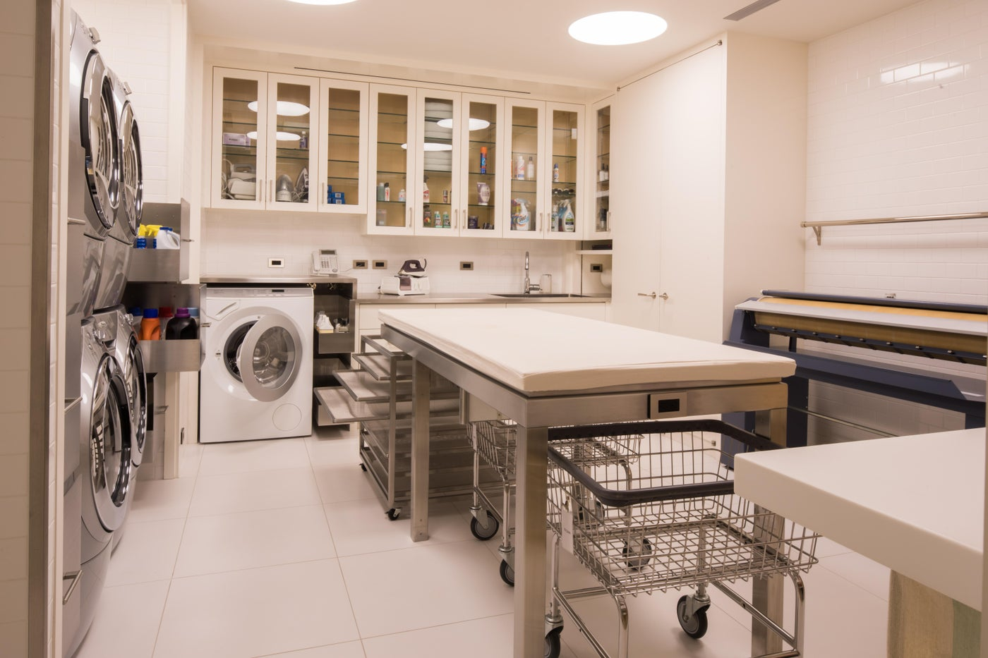 The utilitarian, organized white laundry room has storage for everything.