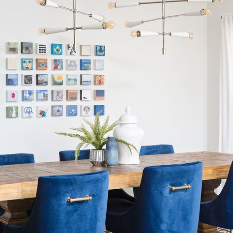 Contemporary linear chandelier, blue velvet chairs & rustic modern dining table.