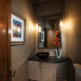 Dramatic powder room with textured wallcovering, glass vessel sink in Scottsdale