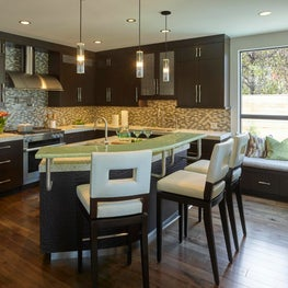 Kitchen island featuring leather tile face, metal toe kick, recycled glass bar