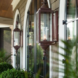 Elliptical Steel French Doors and Shingled Wall with Copper Outdoor Sconces