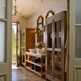 Master bathroom with marble sinks, open wooden vanity, antique armoires, tile