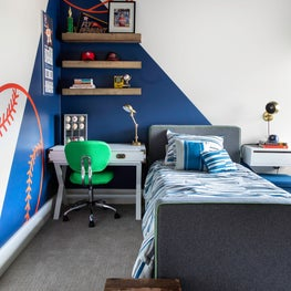 A boys bedroom with blue walls and athletic patterns