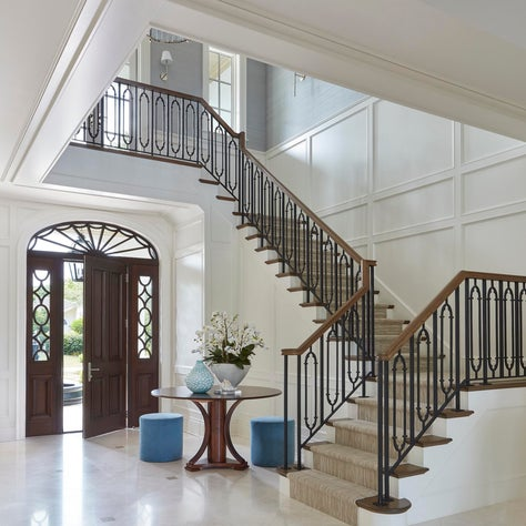 Mediterranean style entry with white backdrop, decorative banister and door trim.