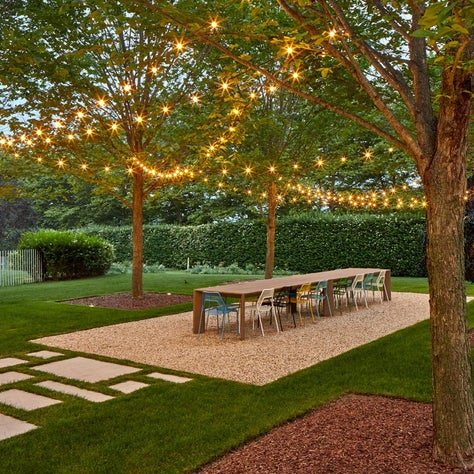 Alfresco dining table beneath a bosque of plane trees and outdoor lighting