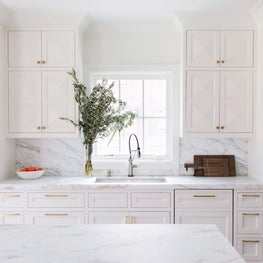 Custom white kitchen with faceted cabinet fronts and expansive Calacatta Gold island.