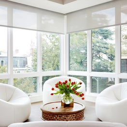 Bright, white seating area with floor-to-ceiling windows, bucket chairs, shades