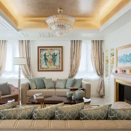 Luxurious and elegant living room  decor in a soft color palette and with a gold-leaf gilded ceiling.