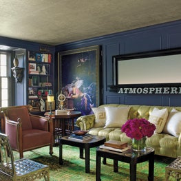 Library with lacquered aubergine paneled walls, custom Chesterfield sofa, Biedermeier armchair, and Gothic sidechair