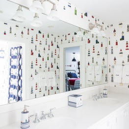 Guest bathroom features nautical lighthouse patterned wallpaper