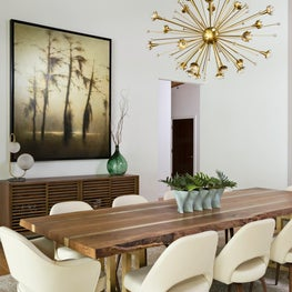 """This contemporary dining room features Jonathan Adler's """"Sputnik"""" chandelier sparkles above Eero Saarinen chairs from DWR that line the dining room's trestle table."""
