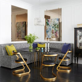 Glamorous breakfast area with banquette and gold Art Deco chairs