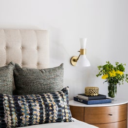Guest bedroom with a tufted headboard and acorn colored nightstand