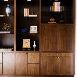Dark wood bookshelf in a mid-century modern study room