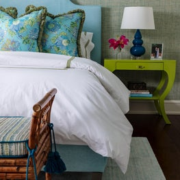 Grass cloth wallpaper and repainted green night table add a tropical vibe.