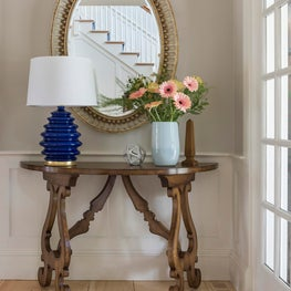 Demilune carved table, blue lamp, oval mirror, striped rug entryway