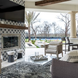 Exterior living space with tiled fireplace and spacious seating in Houston, Texas