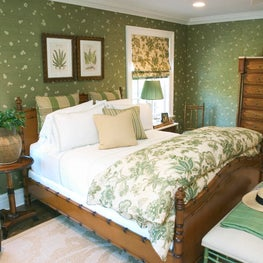 A green& white color palette compliments the warm wood furniture in this bedroom