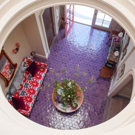View onto foyer with purple tiling, bright couch