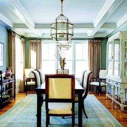 Coffered ceiling, wainscoting, and pair of oversized lanterns over the table