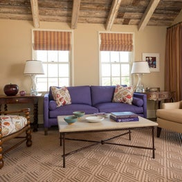 Adorable and colorful cottage living room with exposed wood beams