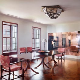 A corset dining table & Dessin Fournir chairs complimented by parquet flooring