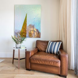 A painting by Abby Sin creates bold color and metallic effects in the cozy reading nook. The upcycled leather chair was paired with a contemporary walnut and marble side table and a pillow made of a textile inspired by Mount Entoto, a peak in Ethiopia.