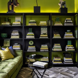 Acid green lacquer walls and LED up-lighting add a jolt of color to this den.