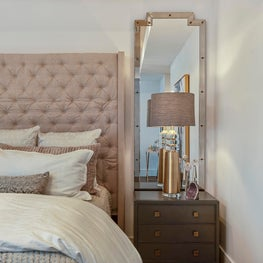Blush upholstered bed with framed floor length mirror and chic bedside lamp.