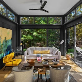 Modern living room with yellow accents, floor to ceiling windows, black walls