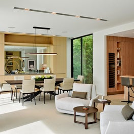 A neutral living room opens to a dining area with custom fixture by Studio Endo.
