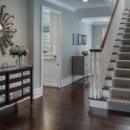 Welcoming Foyer with Eclectic Accents plays off of Tailored Pinstriped Stair Runner