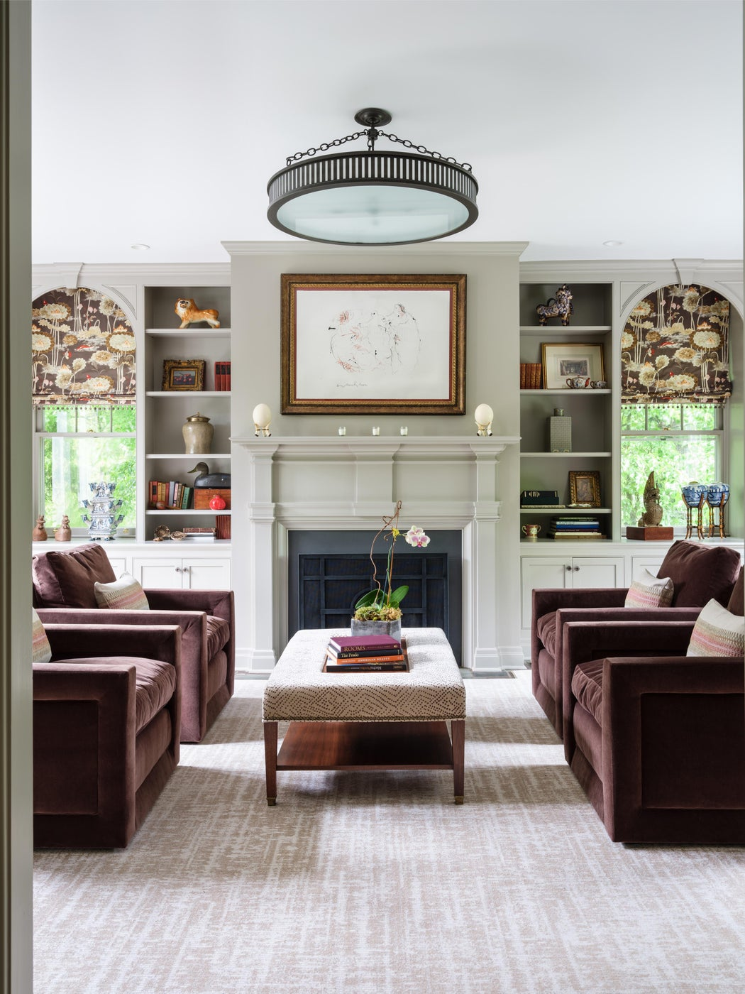 Library with velvet chairs, custom ottoman coffee table and floral print fabric.