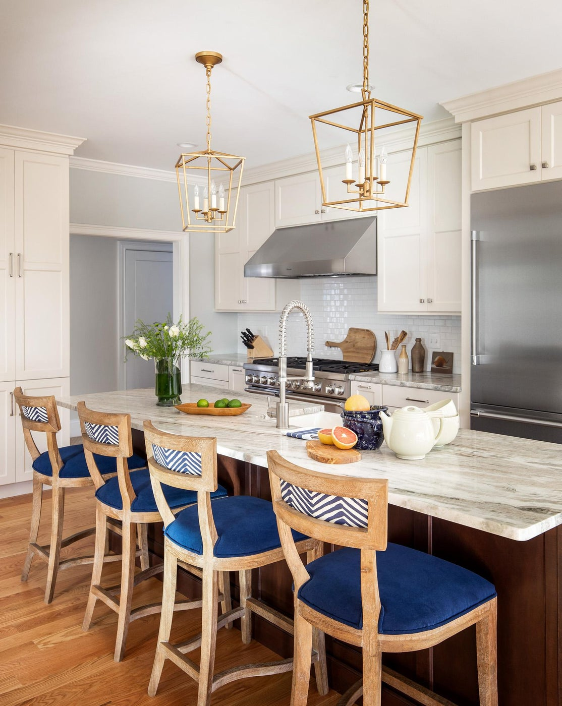 Kitchen island w navy and patterned counter stools, brass lanterns