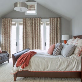 Large guest bedroom with orange and red accents