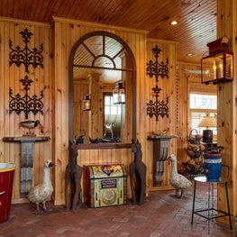 Entry hall to rustic family room with vintage mirror an wood paneled walls.