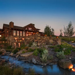 Elegant and expansive log cabin-inspired facade with stream water feature