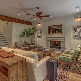 Shiplap walls with concealed storage provided on either side of the fireplace