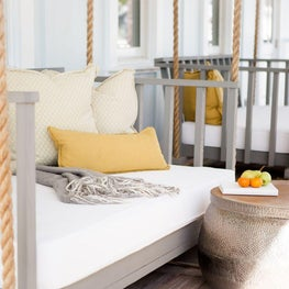 Front porch bed swings with yellow pillows on Florida coast