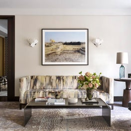Artful living room with modern furniture, marble sconces, and glass lamps.
