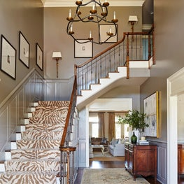 Entry foyer with Stark animal print runner and dark moody gloss walls.