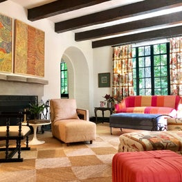 The Spanish Colonial architecture sets a chic backdrop for a fun and comfortable space featuring vibrant art, lush upholstery, and festive textiles by Jim Thompson and Fortuny.