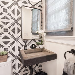 """Black and White Powder Room that creates a """"wow"""" with black hardware and cement tiles."""