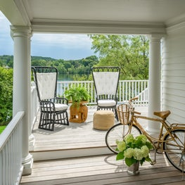 Porch with High Back Chairs, Gold Bicycle, and a Lake View