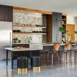 Modern family residence sleek styled kitchen featuring a glass mosaic backsplash and walnut custom cabinetry.